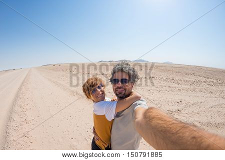 Adult Couple Taking Selfie On Gravel Road In The Namib Desert, Namib Naukluft National Park, Main Tr