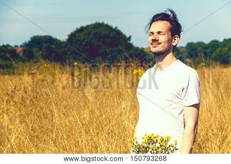 Man Standing In Field Of Dry Grass