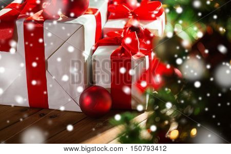 christmas, holidays, presents, new year and celebration concept - close up of gift boxes and red balls under x-mas tree on wooden floor