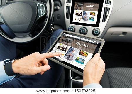 transport, business trip, technology, blogging and people concept - close up of male hands holding tablet pc computer with internet blog page on screen in car