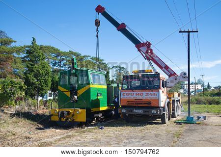 DALAT, VIETNAM - DECEMBER 27, 2015: Renovation of the locomotive with the aid of the crane on the chassis of Russian Kamaz-64112 car at the railway station of Dalat city