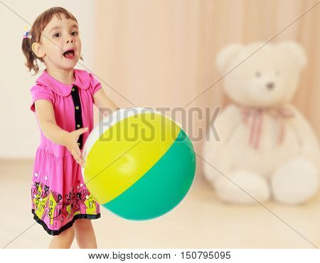 Emotional little girl with pigtails on the head , in a pink dress. Girl catches with hands a large, inflatable striped ball.On blurred background children's room in which sits a large Teddy bear.