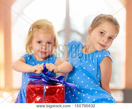 Two charming little girls , sisters, in identical blue dresses with polka dots. Girl looking at gifts Packed in beautiful red paper tied with a bow.