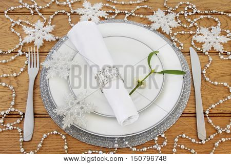 Christmas dinner table setting with white plates, cutlery, linen serviette with ring, mistletoe, silver snowflake and bead  bauble decorations on oak background.