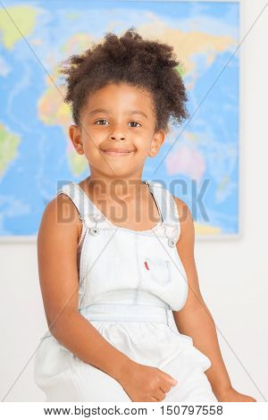 Cute preschool girl with world mapat the class room