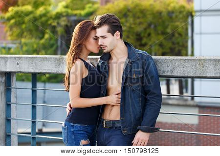 Sensual young couple posing outdoor brunette woman seduce man whispering