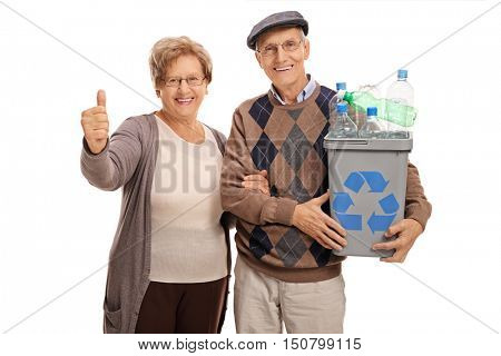 Elderly man holding a recycling bin full of plastic bottles and a mature woman giving a thumb up isolated on white background
