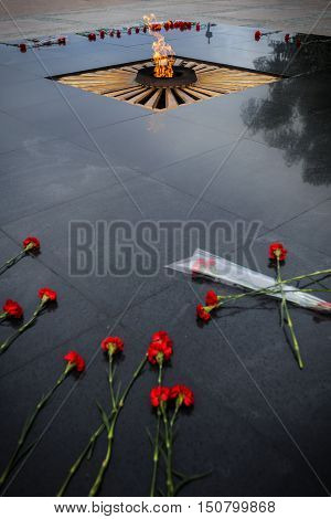 Eternal flame and flowers on granite dark skies reflected in granite