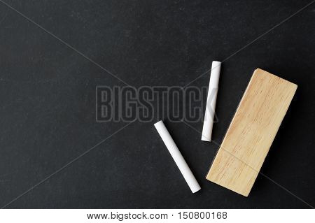 chalk and eraser on chalkboard with copy space ready for your message