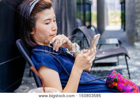 Beautiful Asian woman happy Waiting for coffee and use smartphone in Coffee shop