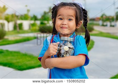 portrait of happy young little girl hugs coins glass bottle ,saving money concept ,Education, school concept. Junior Savings Account concept