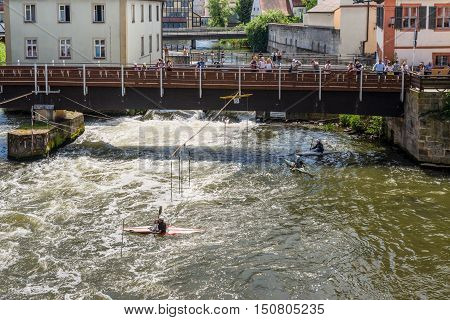 Bamberg Germany - May 22 2016: Tourists on a bridge and kayak slalom on the River Regnitz Bamberg Bavaria Germany Europe. The historic city center is a listed UNESCO world heritage site.