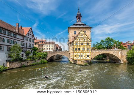 Bamberg Germany - May 22 2016: Historical city hall of Bamberg on the bridge across the river Regnitz and kayaking in the foreground Bamberg Germany.