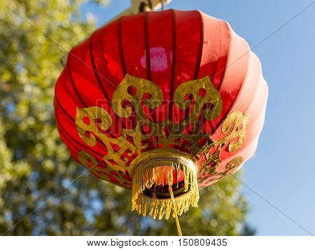 Red chinese lampion with golden ornaments in front of blue sky
