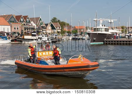 URK THE NETHERLANDS - SEP 24: Rescue workers at a lifeboat on September 24 2016 in the harbor of Urk the Netherlands