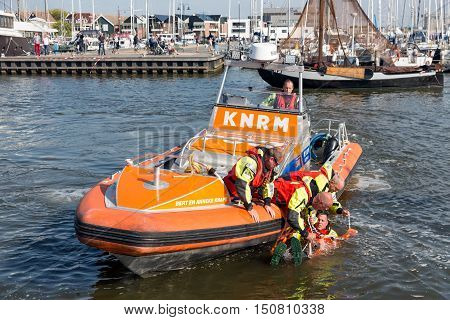URK THE NETHERLANDS - SEP 24: Rescue workers at lifeboat showing how to save people out of the water on September 24 2016 in the harbor of Urk the Netherlands