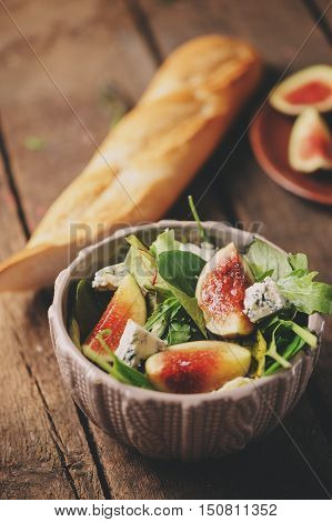 figs salad with blue cheese and ruccola on rustic wooden background. Homemade healthy food with seasonal fruits