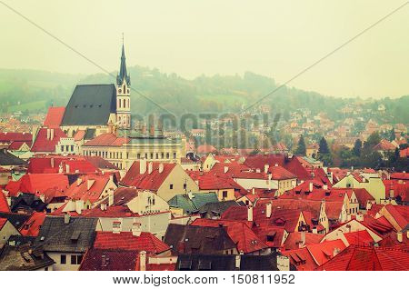 Cesky Krumlov - a famous czech historical beautiful town frome above, travel vintage hipster background with red roofs and chapel