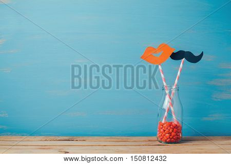 Valentine's day romantic background. Retro bottle and strows with paper mustache and lips.