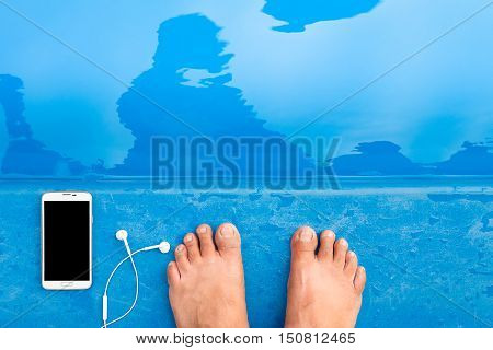 Smartphone with Earphones and feet near edge of swimming pool.