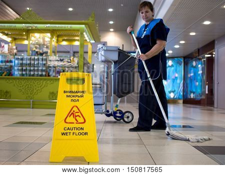 Moscow, Russia - November 07, 2015: Elderly woman - the cleaning lady cleans tile floor in the hall of Domodedovo airport.