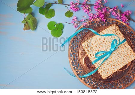 Passover spring holiday background with matzoh seder plate and flowers. View from above