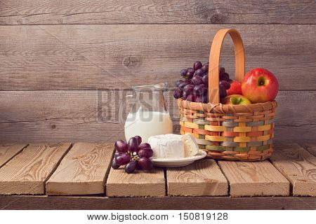Milk cheese and fruit basket on wooden rustic table. Jewish holiday Shavuot celebration