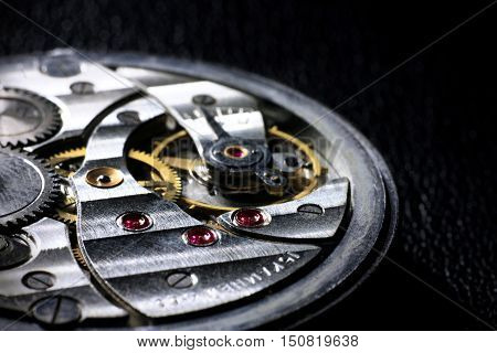 Pocket watch inside close up with wheels springs and rubies on dark background