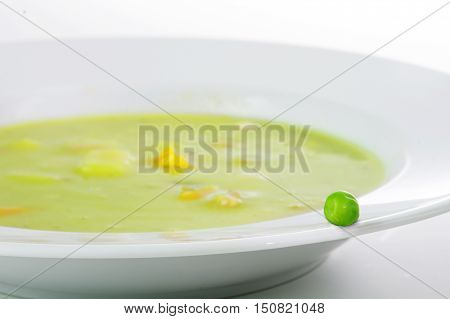 Fresh green pea on the edge of a white plate with vegetable soup close up with selective focus and narrow depth of field