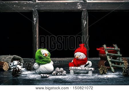 Handmade toy snowman and snowgirl of yarn skeins sawing cookies over black background. Color toning