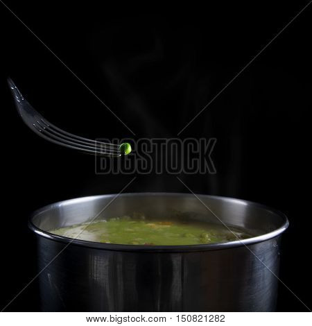 Fresh green pea on a fork over a pot with steamed vegetable soup copy space isolated on a black background selected focus narrow depth of field