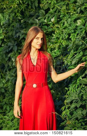 Portrait Of A Beautiful Woman In A Red Dress In Summer Park