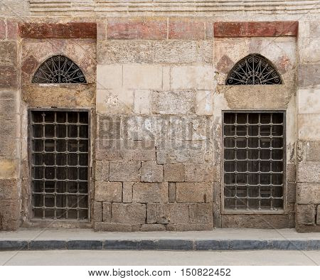 Old abandoned wall with two closed wooden windows covered by broken iron grid El-Dard El-Ahmar Cairo Egypt