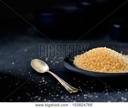 brown sugar in a saucer, vintage teaspoon on a black background