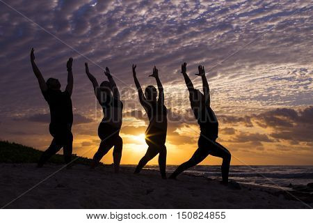 Four people practicing yoga at sunrise at the beach