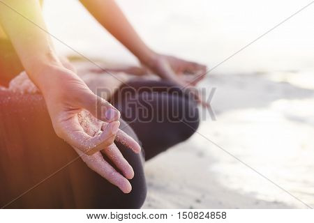 Closeup of woman's hand meditating on the beach