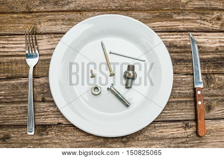 Hardware dinner on plate from screw bolt and nut