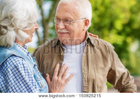 Happy old man and woman are embracing and smiling. They are standing in park on date