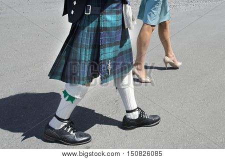 A man dresed up a Scottish kilt‎ and a woman wearing a dress walks down the street.