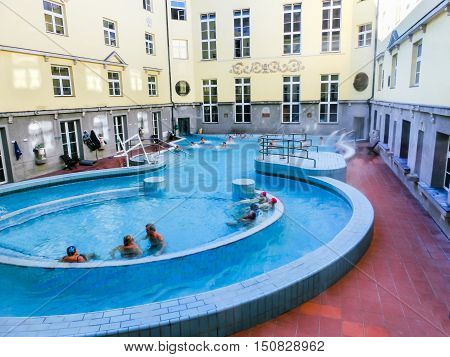 Budapest, Hungary - January 07, 2016: Tourists enjoy at the Lukacs Bath, at historic outdoor thermal bath heated naturally by hot springs, in Budapest, Hungary.