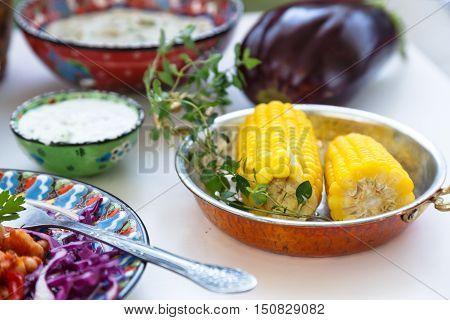 Corn elotes in copper pan. Mediterranian meze.