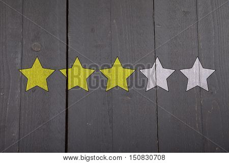 Three yellow ranking stars on black wooden background
