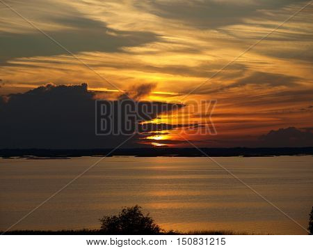 Sunset on a cloudy summer evening by the lake