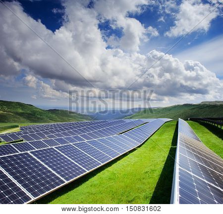 Beautiful modern solar station with blue panels standing in field with green grass and mountains at the horizon under a bright cloudy sky with reflection of clouds in batteries