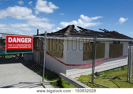 A sign reads - DANGER outside a wood framed home that completely destroyed by fire.