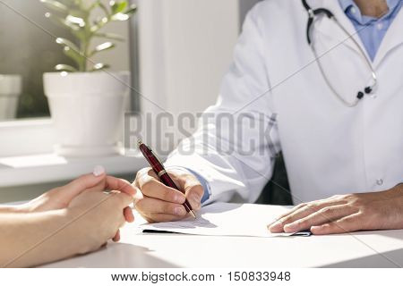 medical consultation - doctor and patient sitting by the table