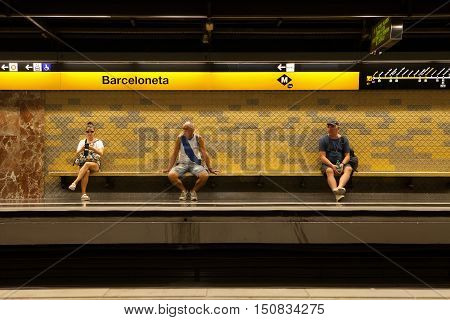 BARCELONA, SPAIN - SEP 13, 2016: Three would-be passengers wait for the metro at Barceloneta.