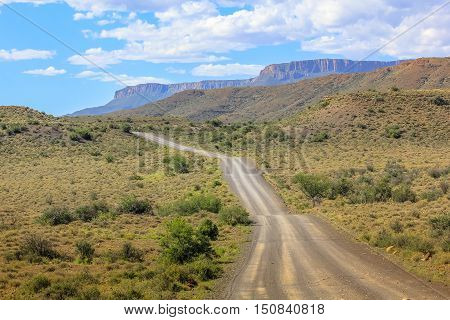Gravel mountain road in the cloudy sky, Karoo National Park in the summer, Western Cape province of South Africa. The parks of South Africa are famous for the magnificent scenery and wildlife.