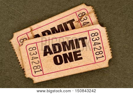 Pair Of Old Torn Admit One Movie Tickets On A Brown Background.
