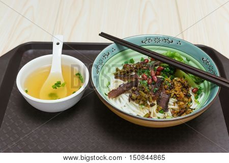 guilin rice noodles with bowl of soup nearby on a plastic plate on white